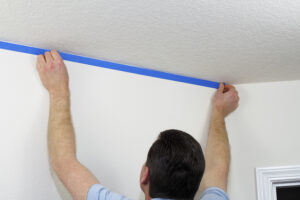 Man preparing to paint ceiling by masking off the wall beneath it with blue painter's tape.